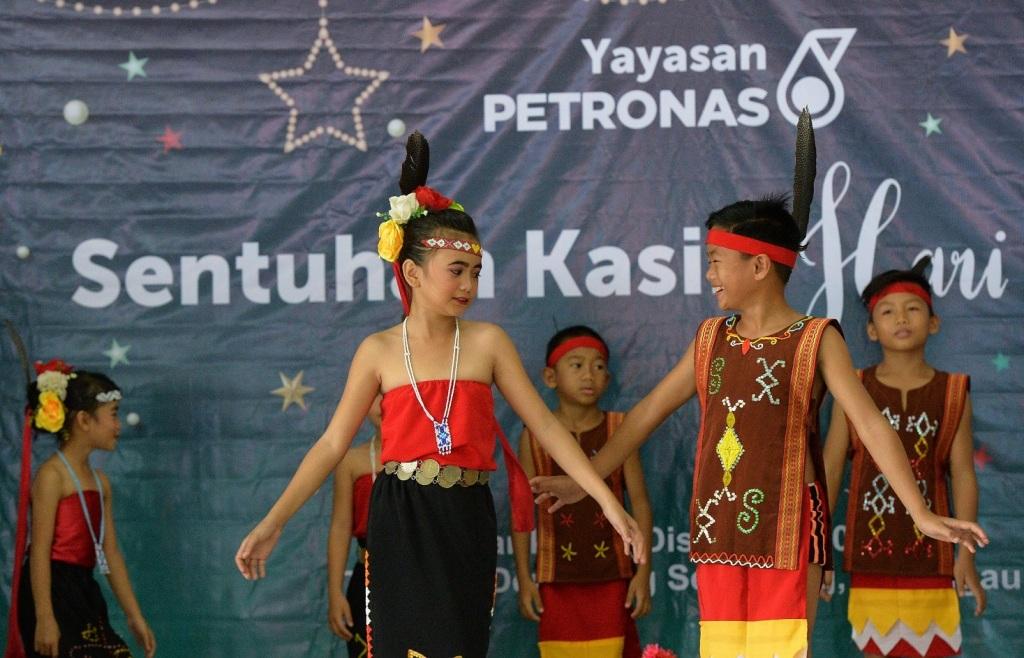 Children enliven the Christmas celebration atmosphere by performing traditional dance at the Petronas Sentuhan Kasih programme at Kampung Senagang, Keningau