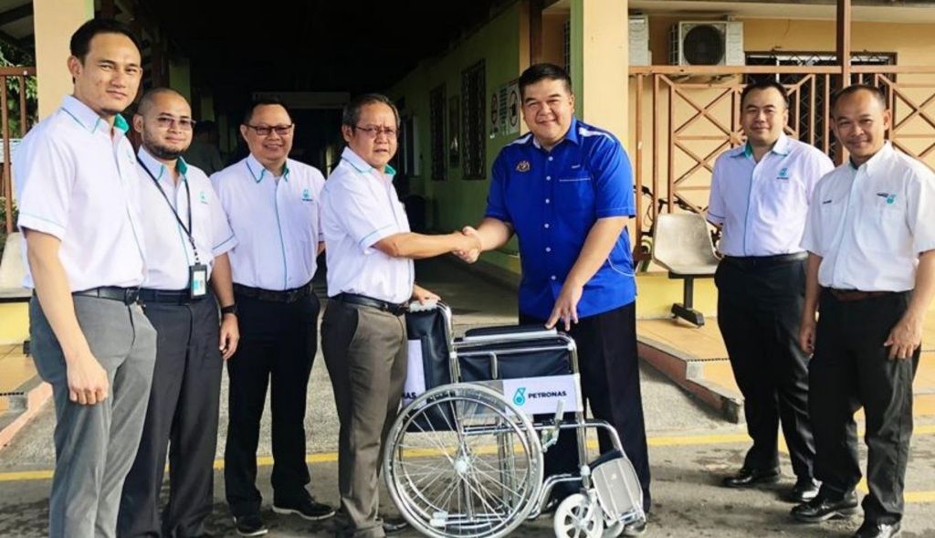 CEO of PETRONAS Chemicals Methanol Sdn Bhd Lawai Jok (4th from left) handing over  wheelchairs to Hospital Nukleus Labuan Director Dr Adnan Musa Balidran.