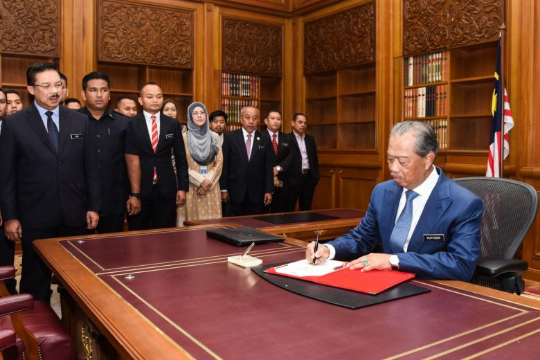 Malaysia's Muhyiddin Yassin signs a document on his first day at the Prime Minister's Office in Putrajaya on March 2, 2020.PHOTO: AFP PHOTO /MALAYSIA'S DEPARTMENT OF INFORMATION/ HAZLINA TAJUDDIN