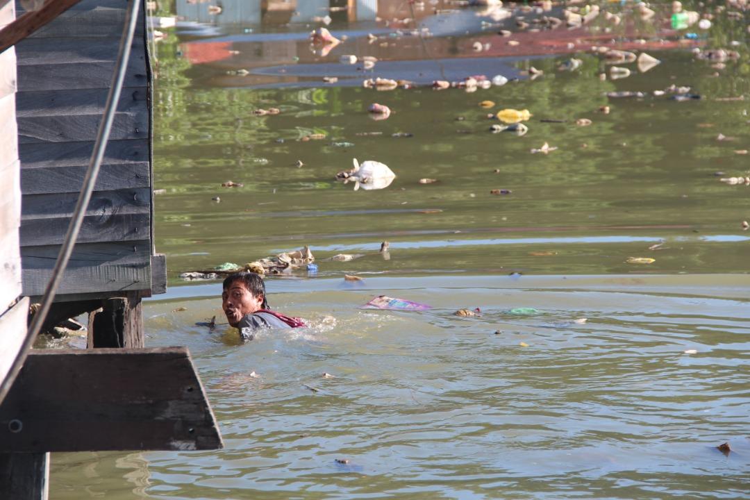 seorang wargaasing berenang di lautan sampah untuk lepas daripada tangkapan pihak berkuasa