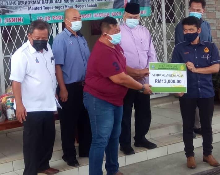 Pengerusi Persatuan Penambang Bot Laju Menumbok Mohamad Sait sambil diperhatikan Arifin dan Limus menerima repalika cek dari Pengurus Besar PBNS Salam Nurilah semasa majlis tersebut