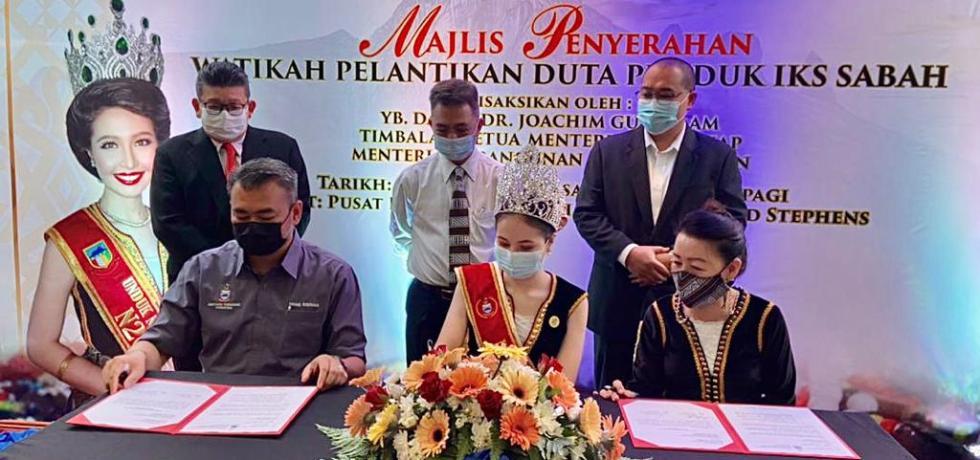 Dr. Joachim (berdiri, tengah) menyaksikan MoU watikah pelantikan Duta Produk IKS Sabah di antara Maya (duduk, tengah) bersama Mohd. Ridzuan, wakil MID (kiri) di Bangunan Tun Fuad Stephen, Kota Kinabalu.
