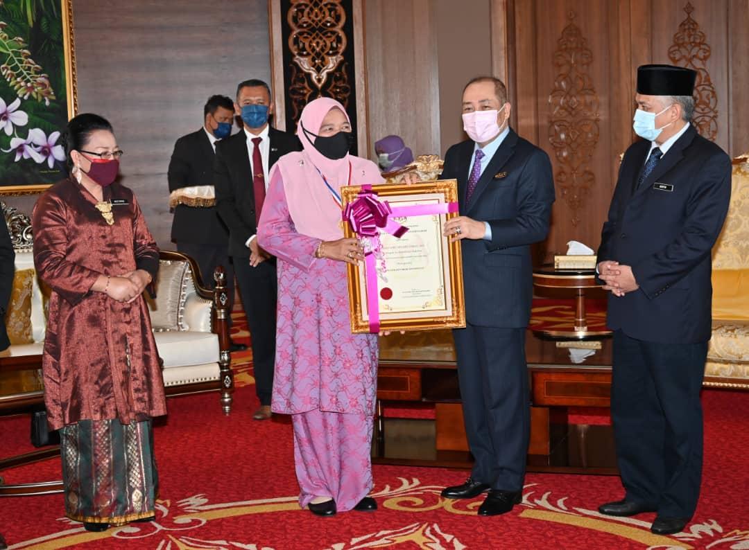 Hajiji menyampaikan sijil anugerah Tokoh Kepimpinan kepada Hajah Maimunah sambil diperhatikan oleh Mohd.Arifin dan Dr.Mistirine.